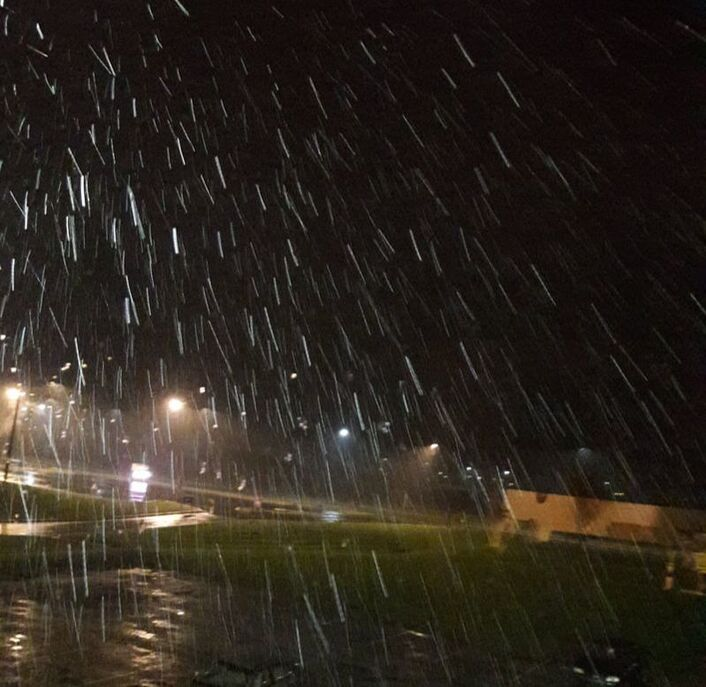 Snow falling outside at night